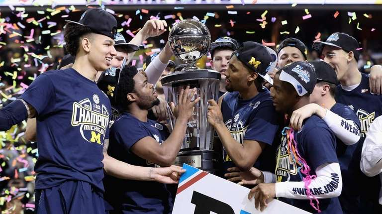 The Michigan Wolverines celebrate with the trophy after