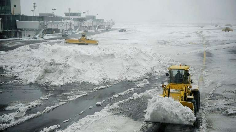Plows clear a tarmac at LaGuardia Airport in