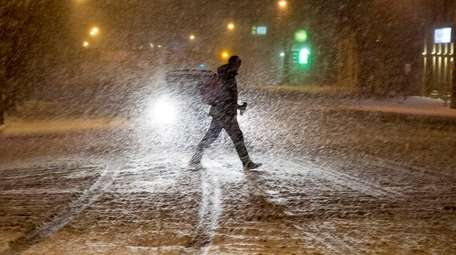 A pedestrian crosses a snow-covered Jericho Turnpike in