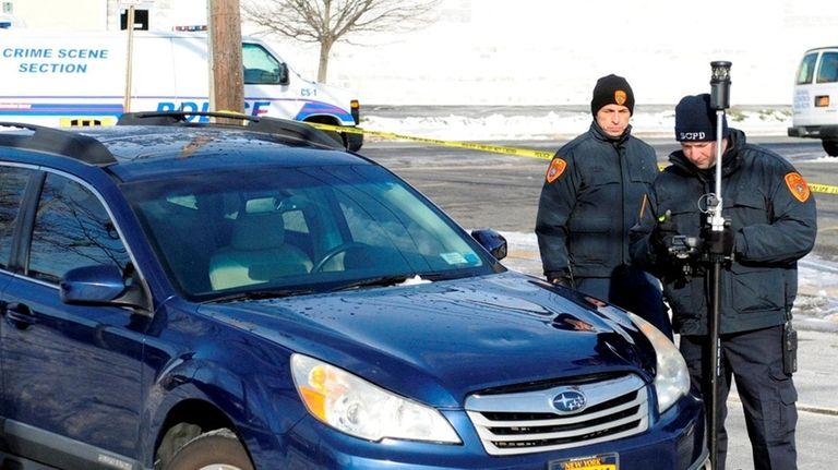 Suffolk County police crime scene investigators survey the