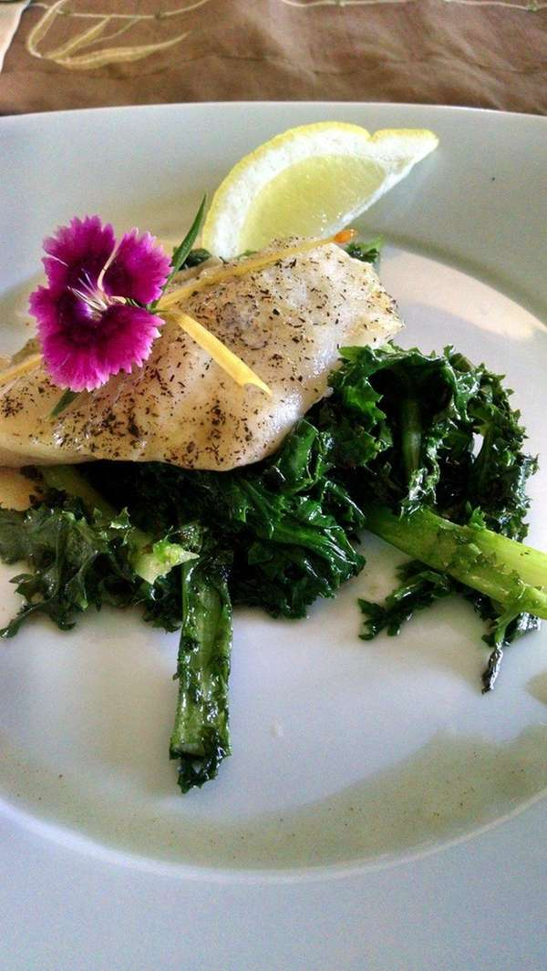 Lemon pepper-crusted sole over sautéed garlic kale is