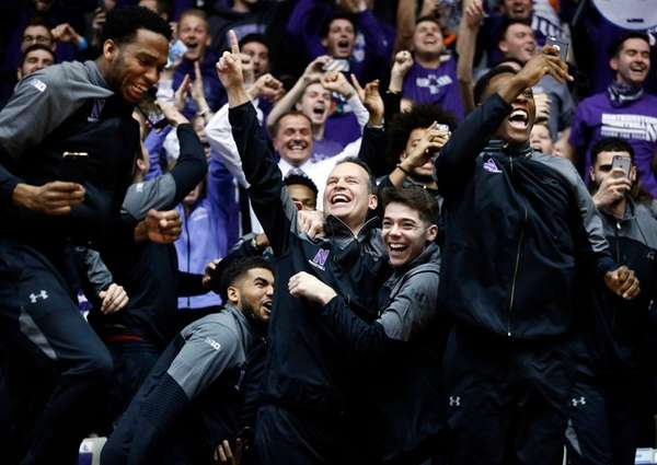 Northwestern coach Chris Collins, center, and players react