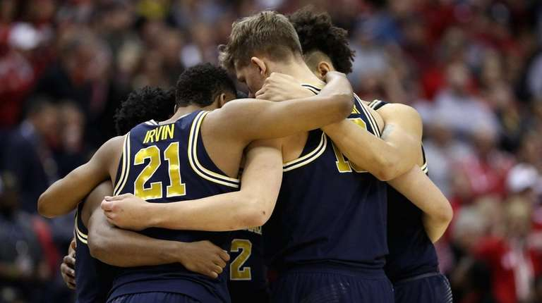 The Michigan Wolverines huddle before the Big Ten
