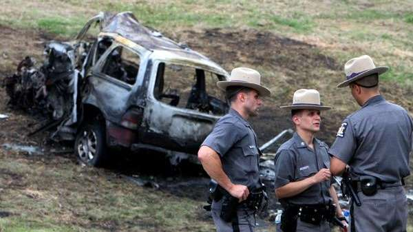 Officers investigate the scene of a three-car accident,