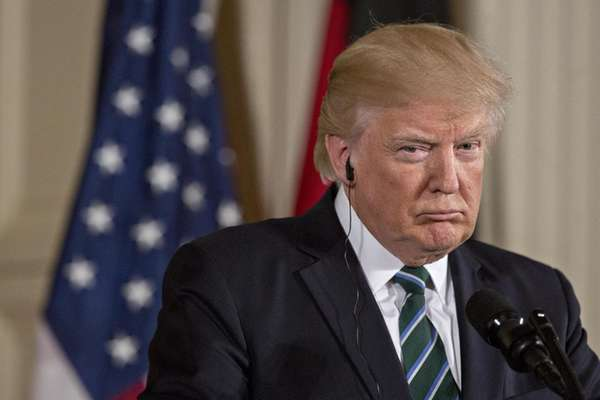 President Donald Trump listens during a news conference