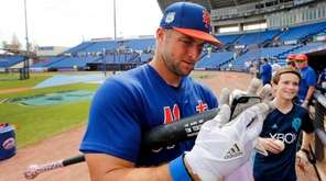 New York Mets' Tim Tebow helps a fan