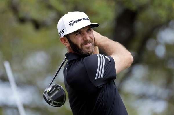 Dustin Johnson watches his shot from the first