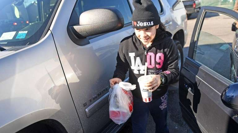 Lydia Pacheco, 11, of Copiague, distributes KFC to
