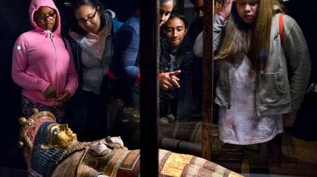 A coffin lid of Egyptian/African origin is viewed