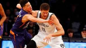Brook Lopez, #11, of the Brooklyn Nets battles
