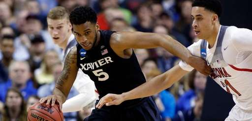 Xavier guard Trevon Bluiett (5) dribbles next to
