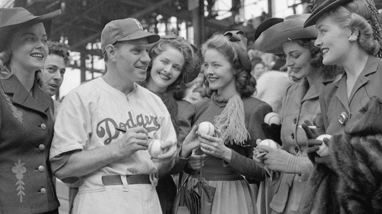 Brooklyn Dodgers manager Leo Durocher signs baseballs for