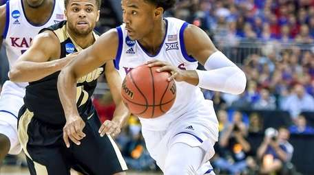 Kansas guard Devonte' Graham, right, drives to the