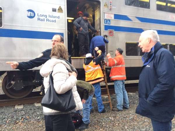 Passengers are helped off a Long Island Rail