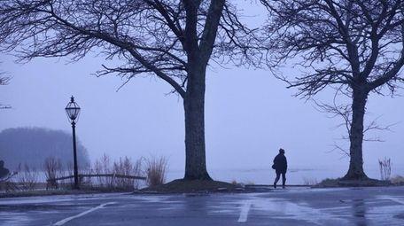 A person walks along Stony Brook Harbor in