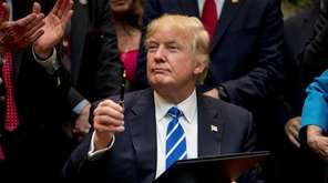 President Donald Trump holds up a pen he