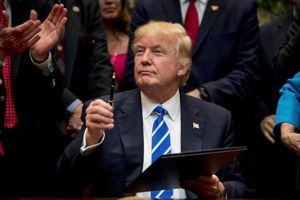 President Donald Trump shows off the pen he