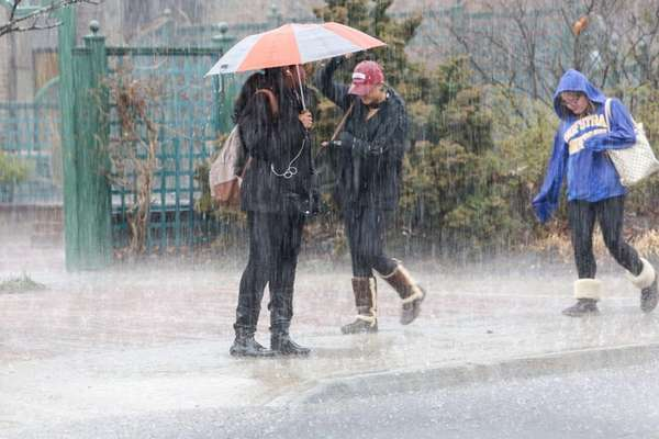 Pedestrians deal with drenching rain as they wait