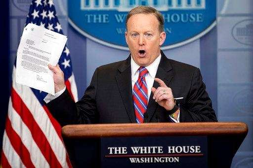 White House press secretary Sean Spicer holds up
