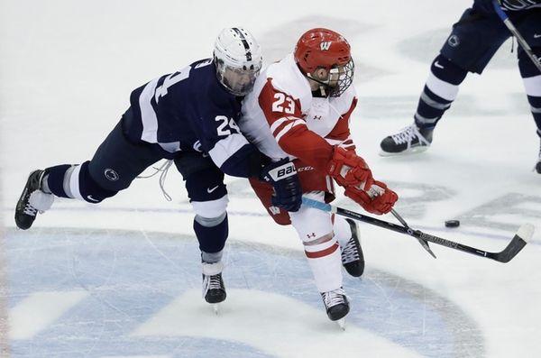 Wisconsin forward Aidan Cavallini (23) passes the puck