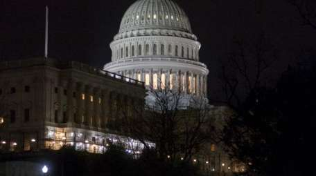 The illuminated Capitol Dome is reflected off the