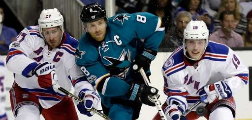San Jose Sharks' Joe Pavelski (8) is defended