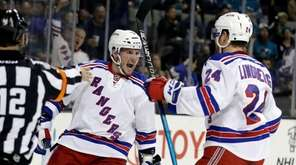 J.T. Miller, left, celebrates his first-period goal with
