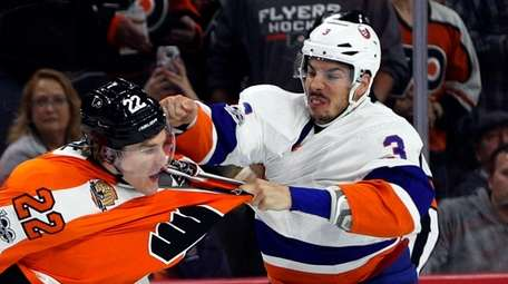 New York Islanders' Travis Hamonic, right, fights with