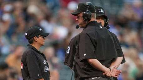 Umpires review a replay on a challenged play