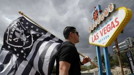 Matt Gutierrez carries a raiders flag by a