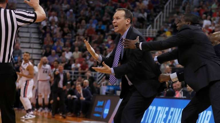 Northwestern coach Chris Collins is held back by