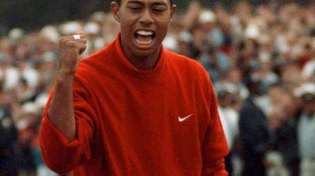 1997 Masters champion Tiger Woods celebrates as he