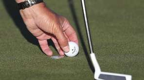 Phil Mickelson marks his golf ball before a