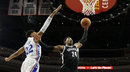 Nets' Rondae Hollis-Jefferson drives between 76ers' Richaun Holmes,