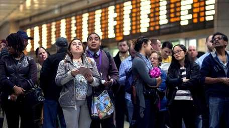 Commuters wait for their trains in Penn Station