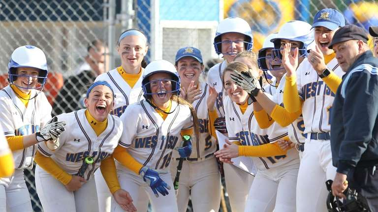 West Islip teammates wait at home plate to