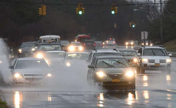 Cars navigate through large puddles on Horseblock Road
