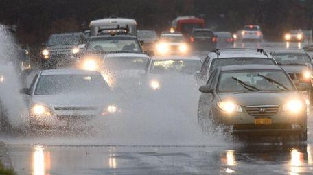 Cars navigate through large puddles on Horseblock Road