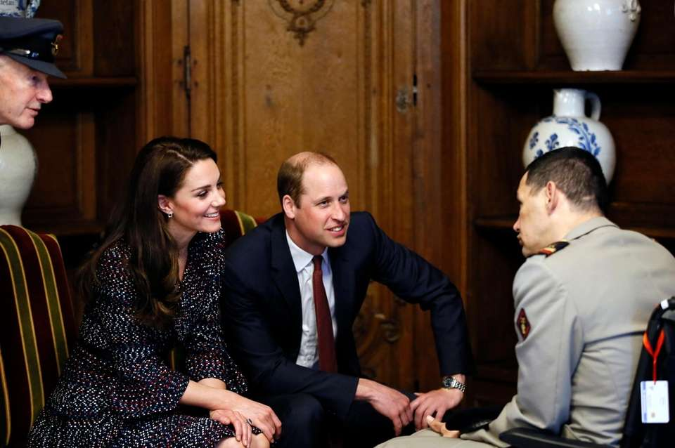 Kate, Duchess of Cambridge, and Prince William listen
