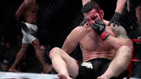 Chris Weidman sits in the octagon after being