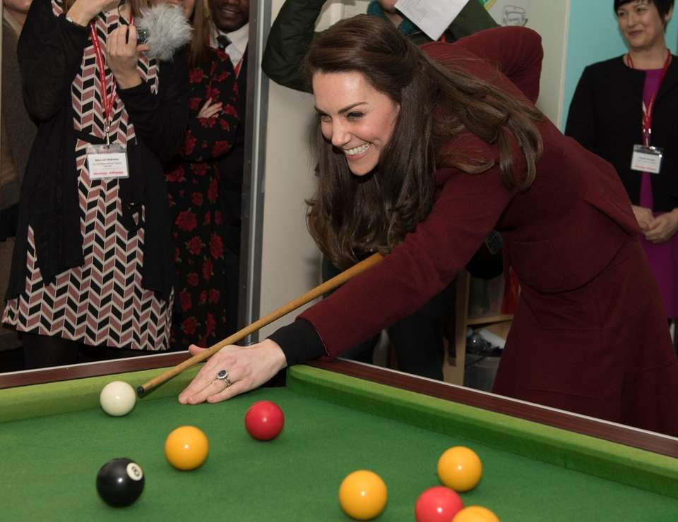 Kate, Duchess of Cambridge, plays pool during her