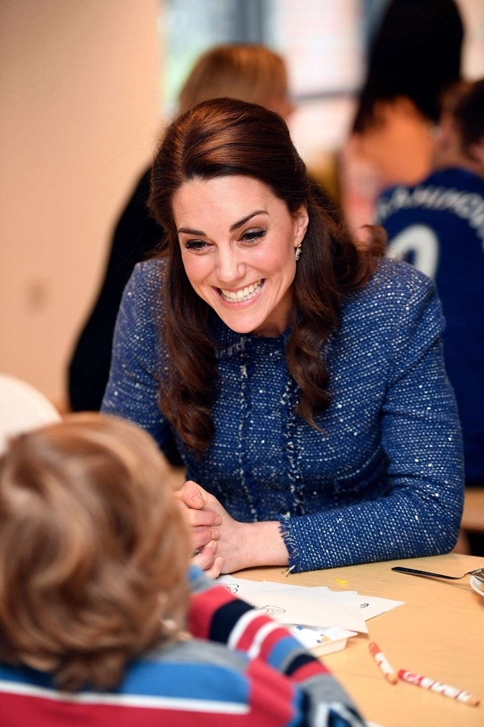 Kate, Duchess of Cambridge, smiles while talking to