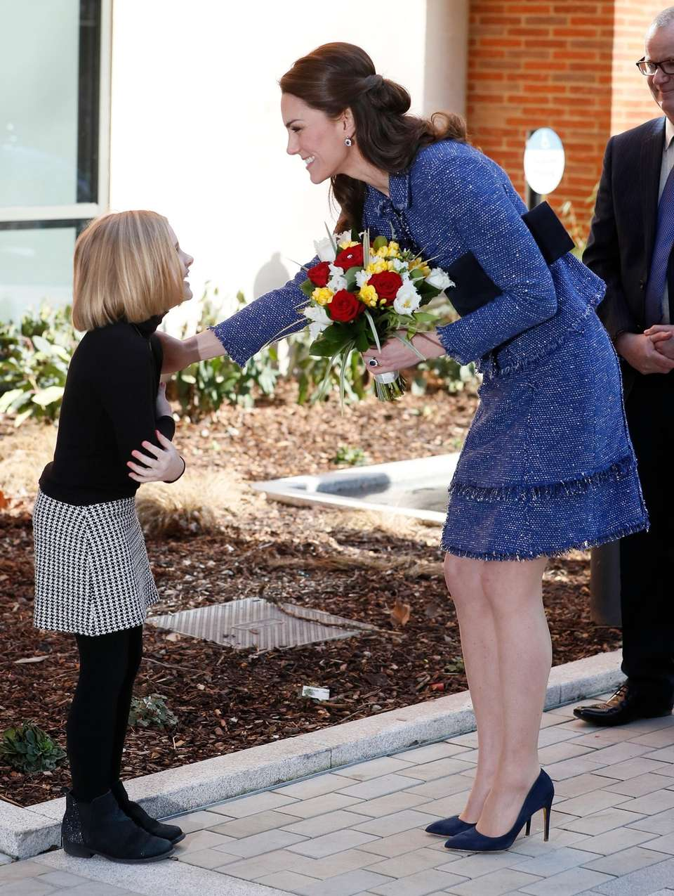 Duchess Kate receives a bouquet of flowers as