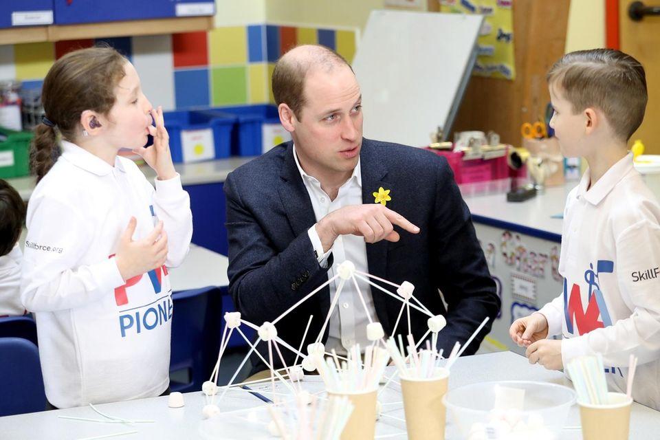 Prince William, Duke of Cambridge, helps children complete