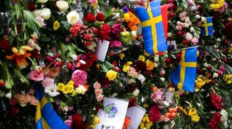 Swedish national flags placed between flowers in fence