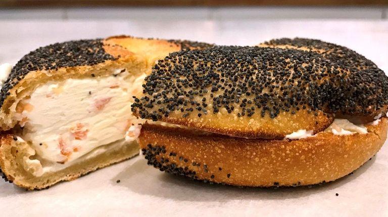 A poppy-seed bagel is schmeared with lox cream
