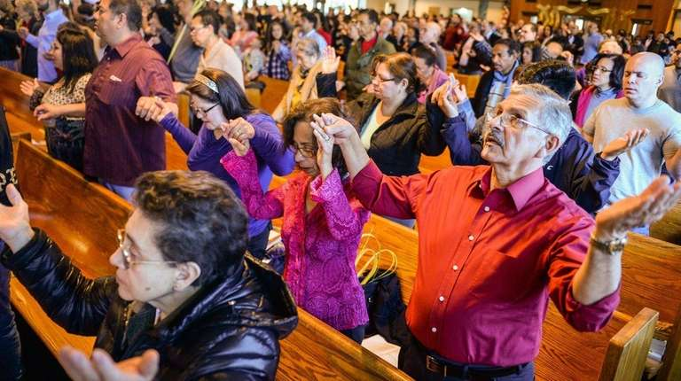 Modesto and Ramona Acevedo, of Bay Shore, pray