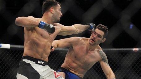 Gerard Mousasi hits Chris Weidman during their bout