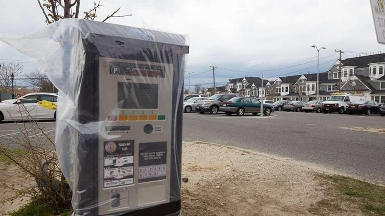 A parking meter covered in plastic sits at