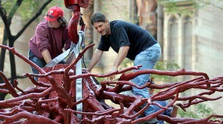 Sculptor Steve Tobin, right, assists a workman in